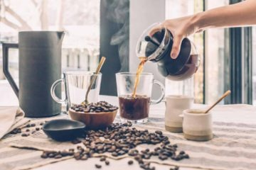 Man pouring in hot coffee in the morning