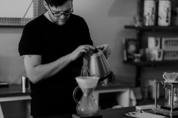 Man pouring hot water in a carafe with a white coffee filter
